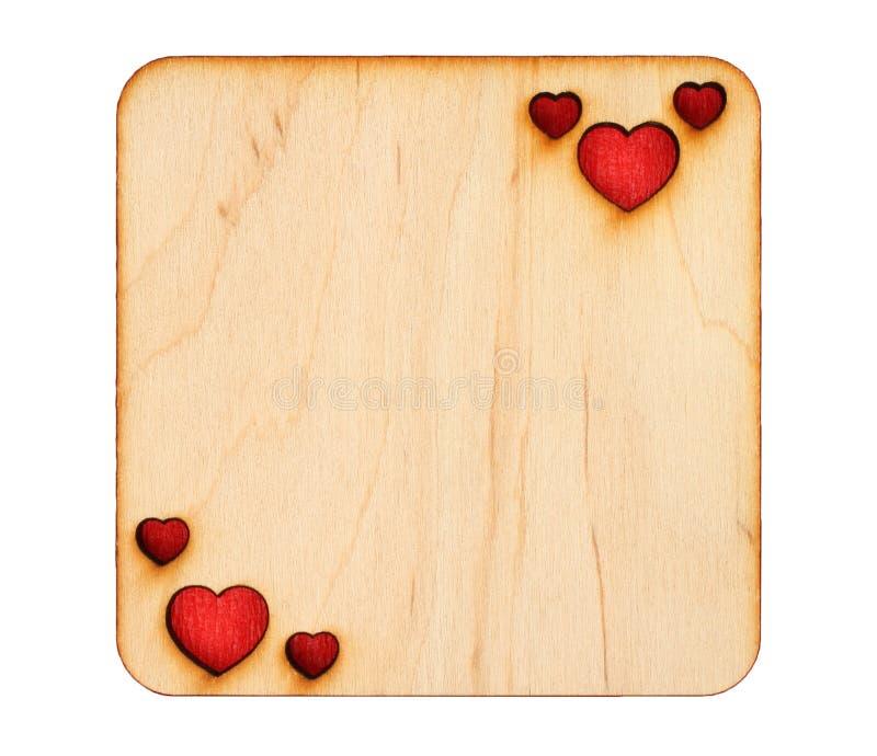 Tarjeta de felicitación de madera con los corazones chamuscados con el papel rojo dentro imagen de archivo