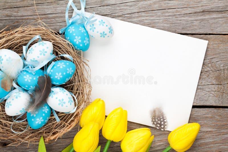 Tarjeta de felicitación de Pascua con los huevos azules y blancos y los tulipanes amarillos foto de archivo libre de regalías