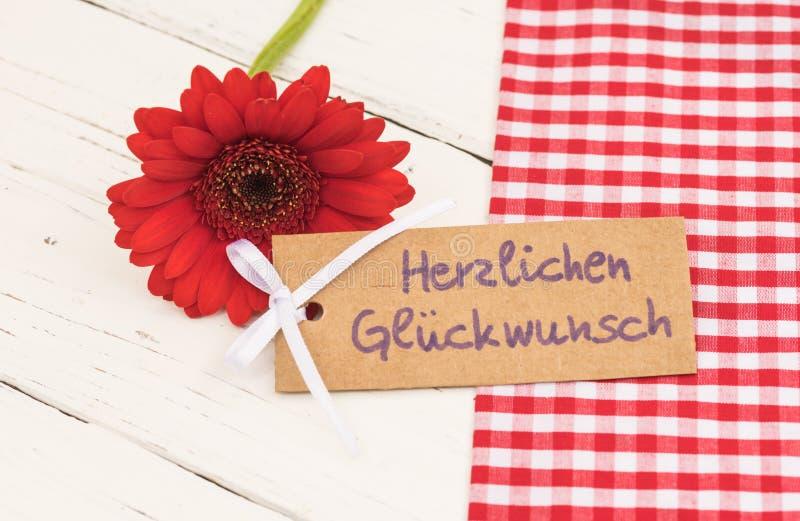 Tarjeta de felicitación del feliz cumpleaños, con el texto alemán Herzlichen Glueckwunsch y la flor roja de la margarita del gerb foto de archivo libre de regalías