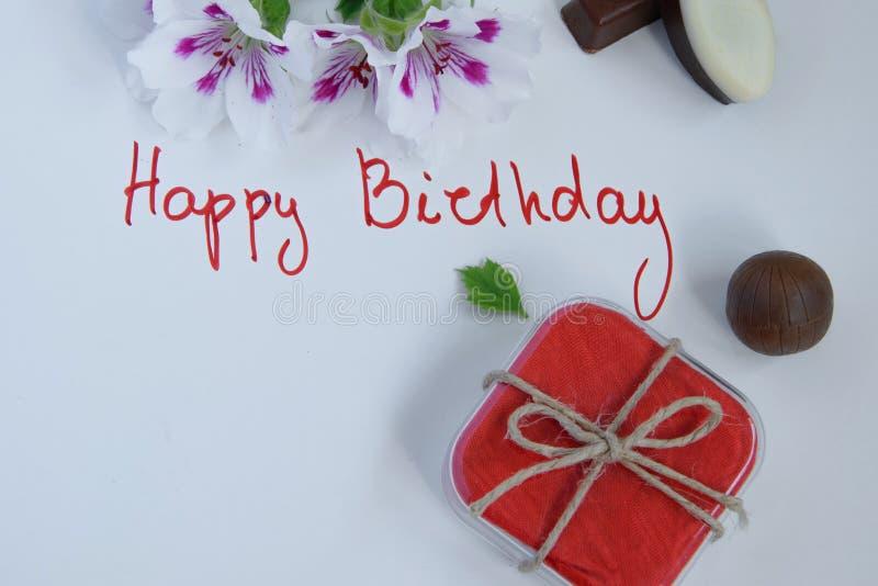 Tarjeta de felicitación del feliz cumpleaños con la caja de regalo, flores frescas fotografía de archivo