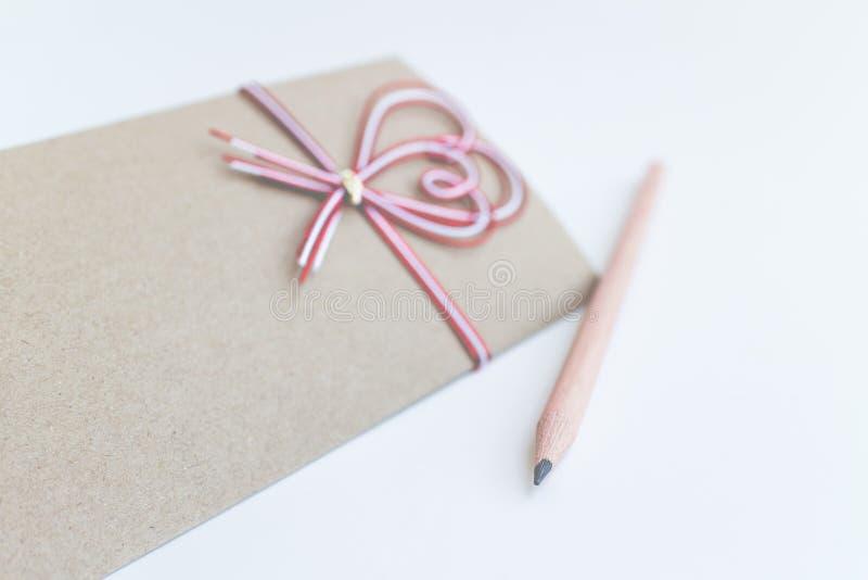 Tarjeta de felicitación en blanco con los corazones rojos y cinta en un fondo blanco para el día de San Valentín fotos de archivo