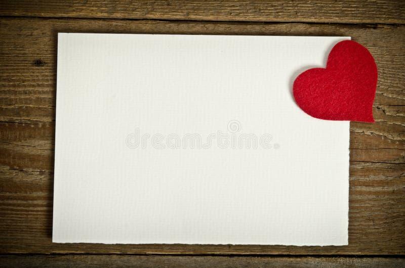 Tarjeta de felicitación en el tablero de madera con el corazón hecho a mano del fieltro imagen de archivo