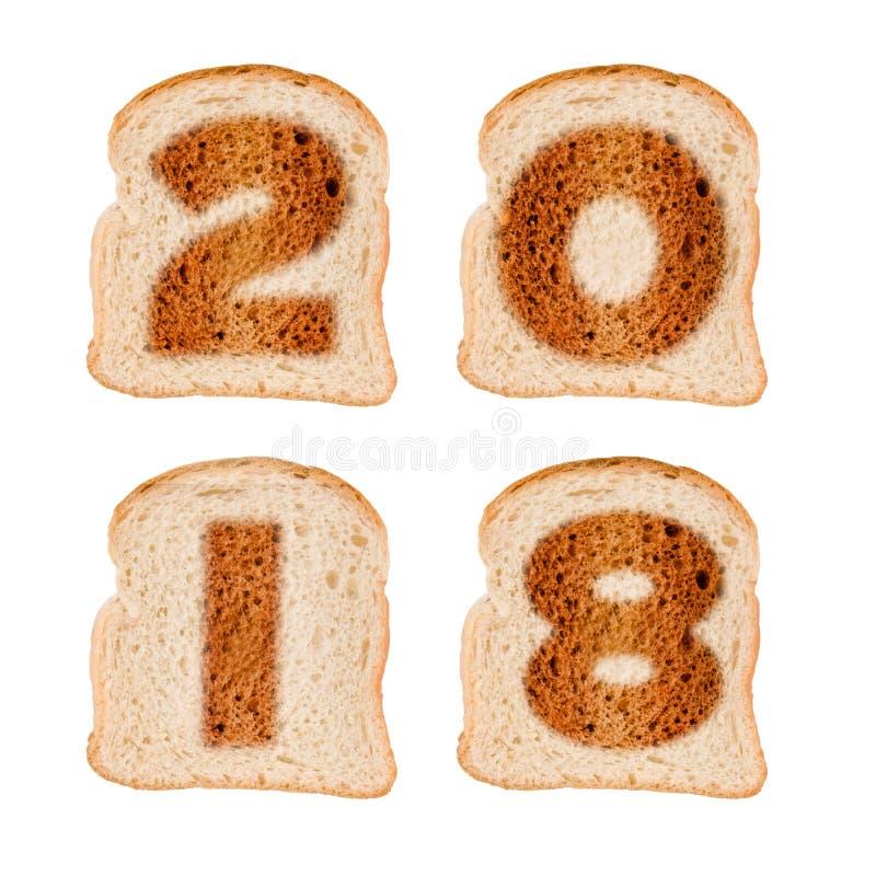 tarjeta 2018 de felicitación en las rebanadas de pan tostadas aisladas en blanco foto de archivo libre de regalías