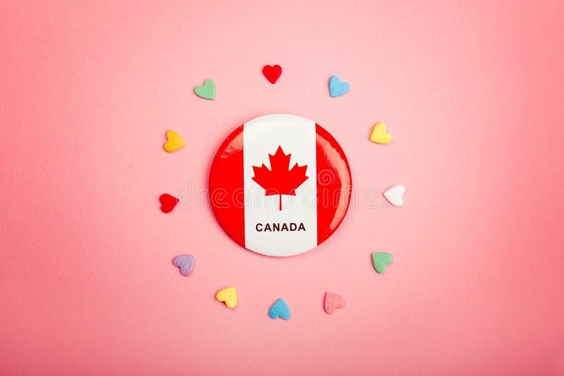 Tarjeta de felicitación feliz del día de Canadá con la bandera canadiense en centro del centro y muchos corazones coloridos de lo fotografía de archivo