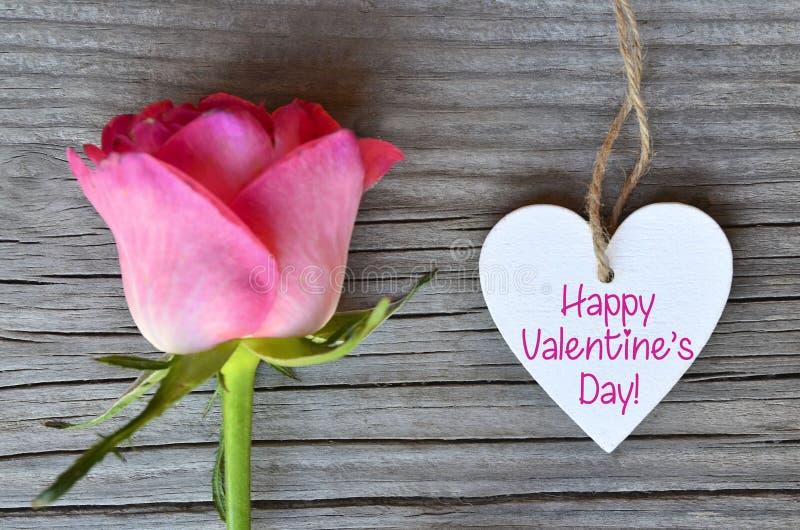 Tarjeta de felicitación feliz del día de tarjeta del día de San Valentín con la rosa rosada y corazón blanco decorativo con el te imagenes de archivo