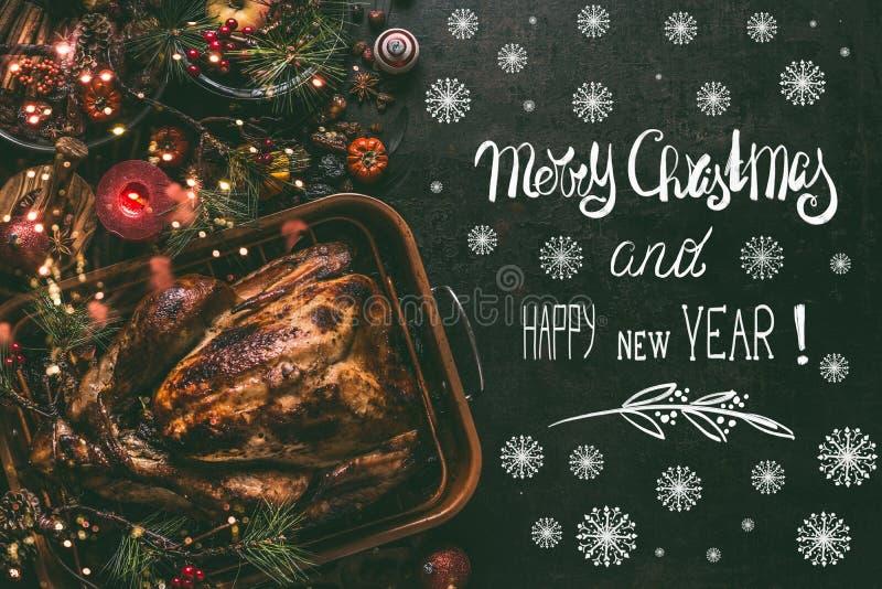 Tarjeta de felicitación de la Feliz Navidad y de la Feliz Año Nuevo con el texto, pavo asado entero en fondo de la tabla de cena  fotografía de archivo