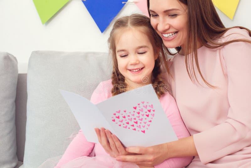 Tarjeta de felicitación de la lectura del concepto de la celebración de la madre que se sienta y de la hija junto en casa fotografía de archivo