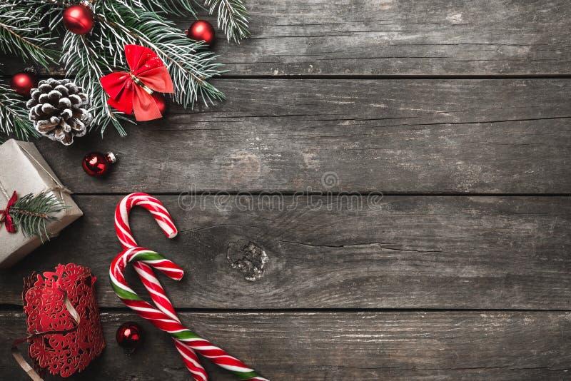 Tarjeta de felicitación de la Navidad en el fondo de madera, ramas del abeto, cono, espacio de mensaje, juguetes, caramelos color imágenes de archivo libres de regalías