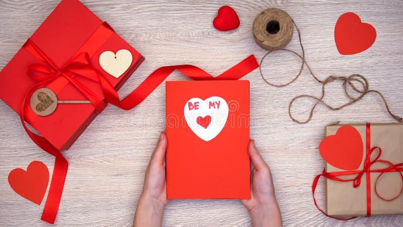 Tarjeta de felicitación que se sostiene femenina con ser mi frase, cajas de regalo hechas a mano en la tabla fotos de archivo libres de regalías