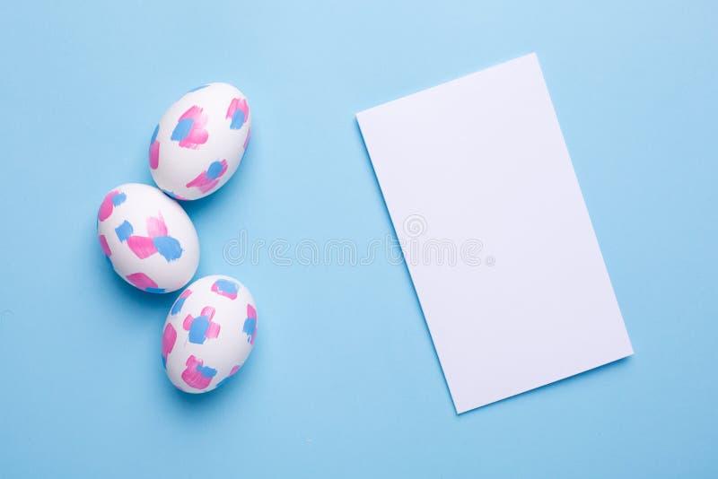 Tarjeta de felicitación y huevos de Pascua con pinceladas de la acuarela imágenes de archivo libres de regalías