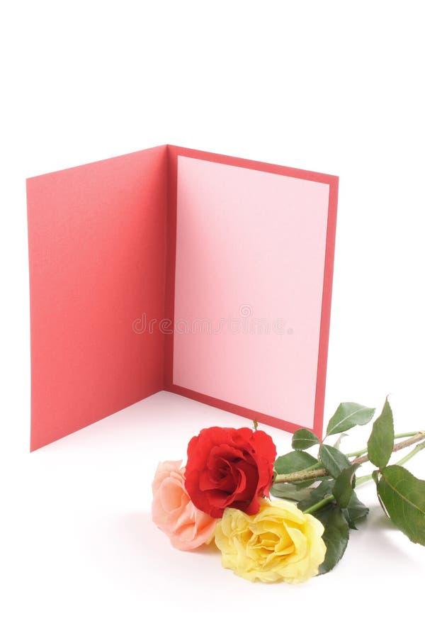 Tarjeta de felicitación y rosas coloreadas fotos de archivo libres de regalías