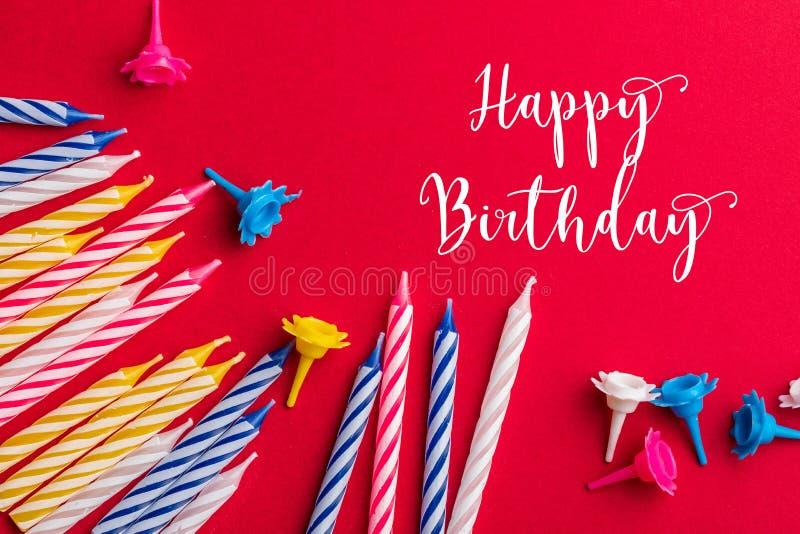 Tarjeta de felicitaci?n del cumplea?os Con las velas muy coloridas rojas, amarillas, blancas y azules en un fondo rojo imágenes de archivo libres de regalías