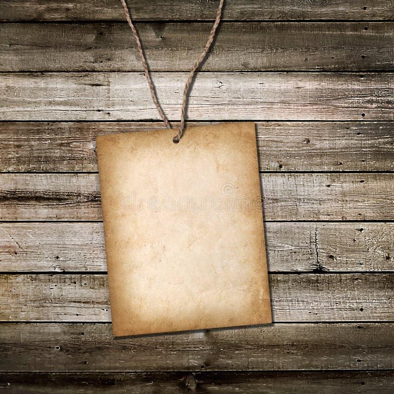 Tarjeta de la cartulina del vintage en una cuerda. Fondo de madera fotografía de archivo libre de regalías