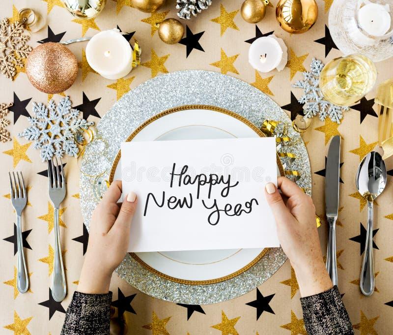 Tarjeta de la Feliz Año Nuevo y ajustes festivos de la tabla imagen de archivo
