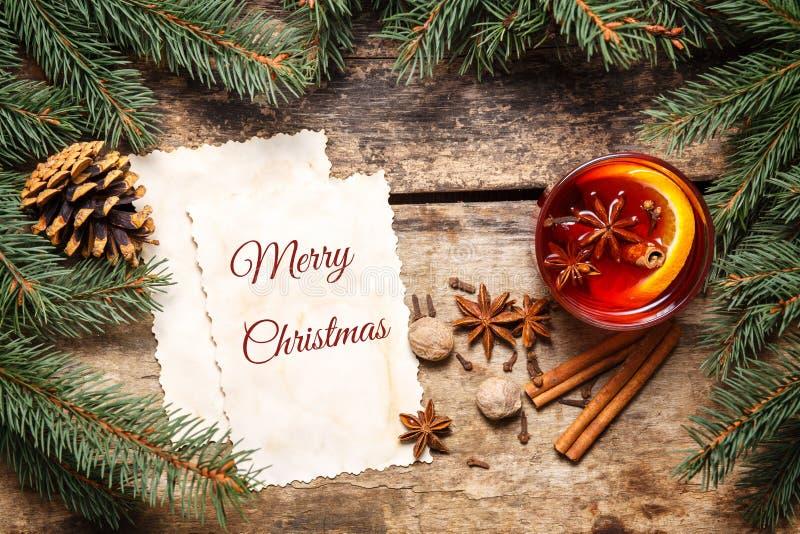 Tarjeta de la Feliz Navidad con el vino reflexionado sobre en la madera imagenes de archivo