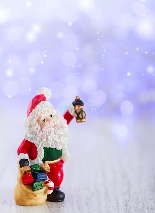 Tarjeta de la Feliz Navidad con la estatuilla de Santa Claus Enciende el fondo con el espacio para el texto Días de fiesta de inv fotos de archivo