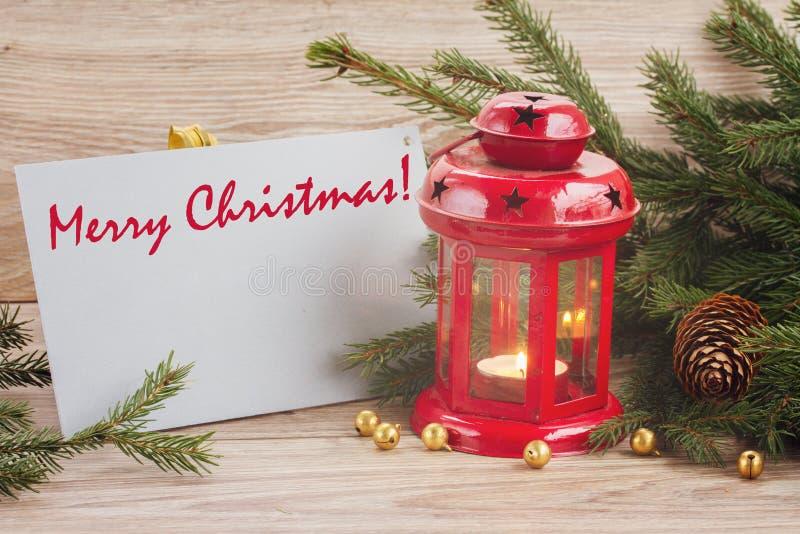 Tarjeta de la Feliz Navidad con la linterna que brilla intensamente roja fotos de archivo