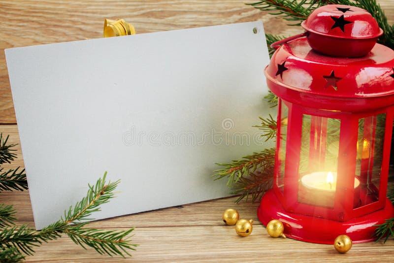 Tarjeta de la Feliz Navidad con la linterna que brilla intensamente roja foto de archivo
