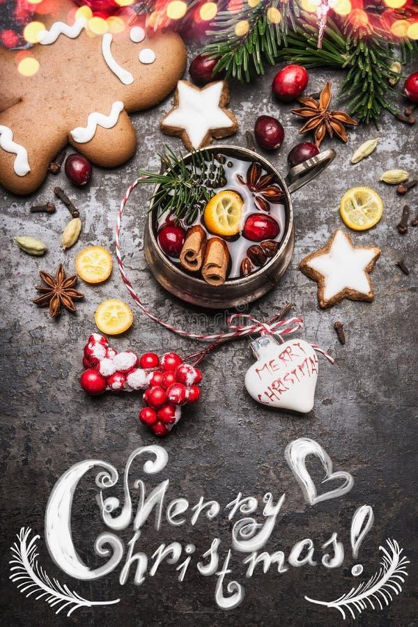Tarjeta de la Feliz Navidad con la taza de vino reflexionado sobre con las especias, las galletas, el hombre de pan de jengibre y fotografía de archivo libre de regalías