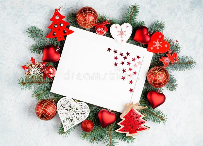 Tarjeta de la Feliz Navidad y de la Feliz A?o Nuevo con la decoraci?n roja foto de archivo