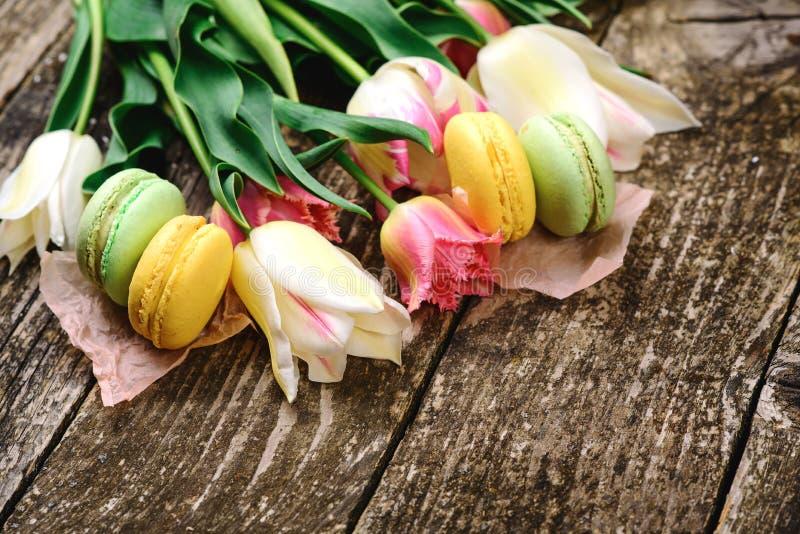 Tarjeta de la primavera con los tulipanes Macarrones y flores coloridos deliciosos de la primavera Día de madres feliz Tortas fra imagen de archivo libre de regalías
