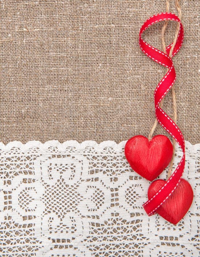 Tarjeta de la tarjeta del día de San Valentín con los corazones de madera y el paño de encaje foto de archivo