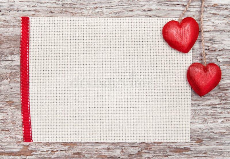 Tarjeta de la tarjeta del día de San Valentín con los corazones en lona foto de archivo