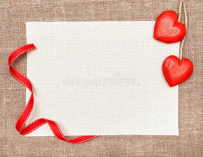 Tarjeta de la tarjeta del día de San Valentín con los corazones y la lona de madera fotografía de archivo libre de regalías