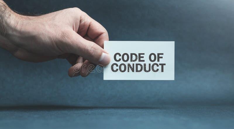 Tarjeta de la tenencia de la mano del hombre Código de conducta foto de archivo