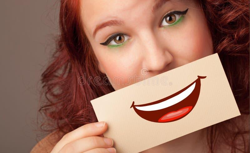 Tarjeta de la tenencia de la persona delante de su boca fotos de archivo