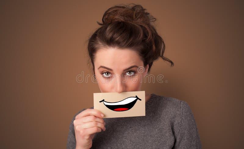 Tarjeta de la tenencia de la persona delante de su boca imagen de archivo
