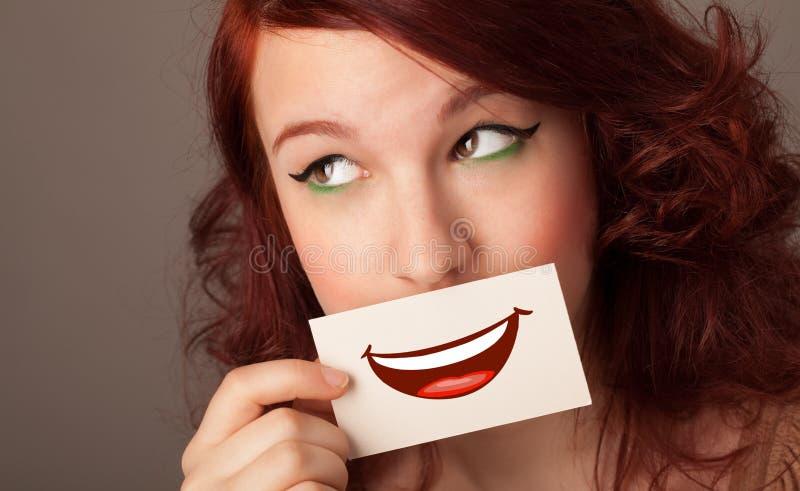 Tarjeta de la tenencia de la persona delante de su boca imagenes de archivo