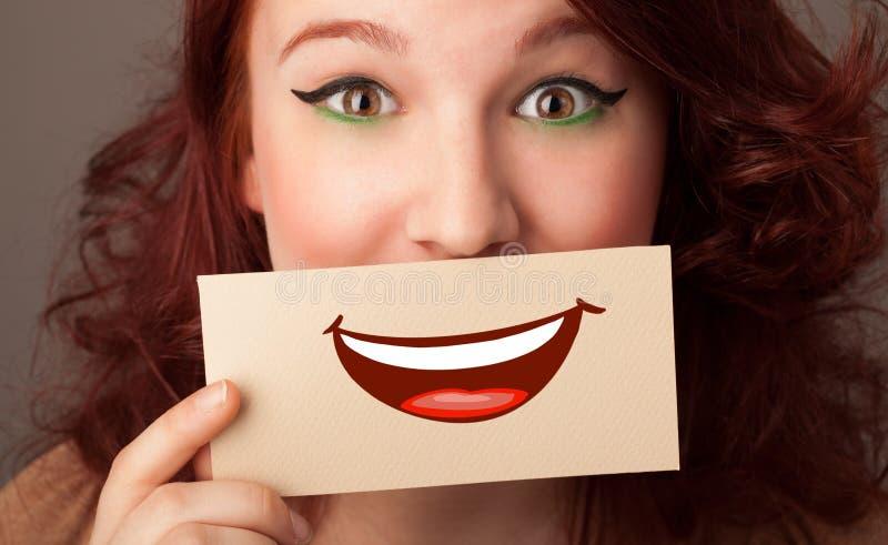 Tarjeta de la tenencia de la persona delante de su boca fotografía de archivo libre de regalías