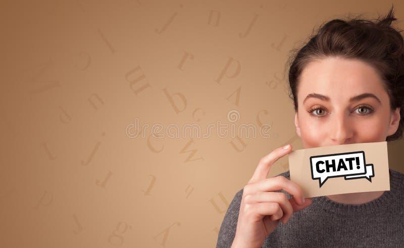Tarjeta de la tenencia de la persona delante de su boca imagen de archivo libre de regalías