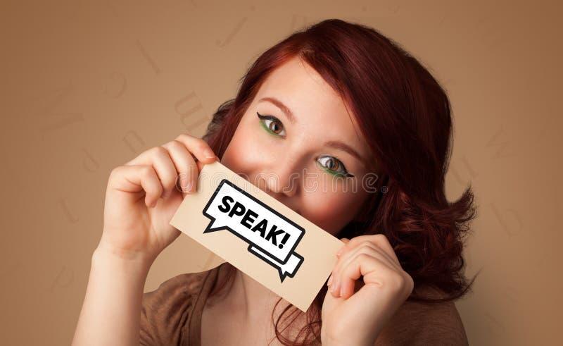 Tarjeta de la tenencia de la persona delante de su boca foto de archivo