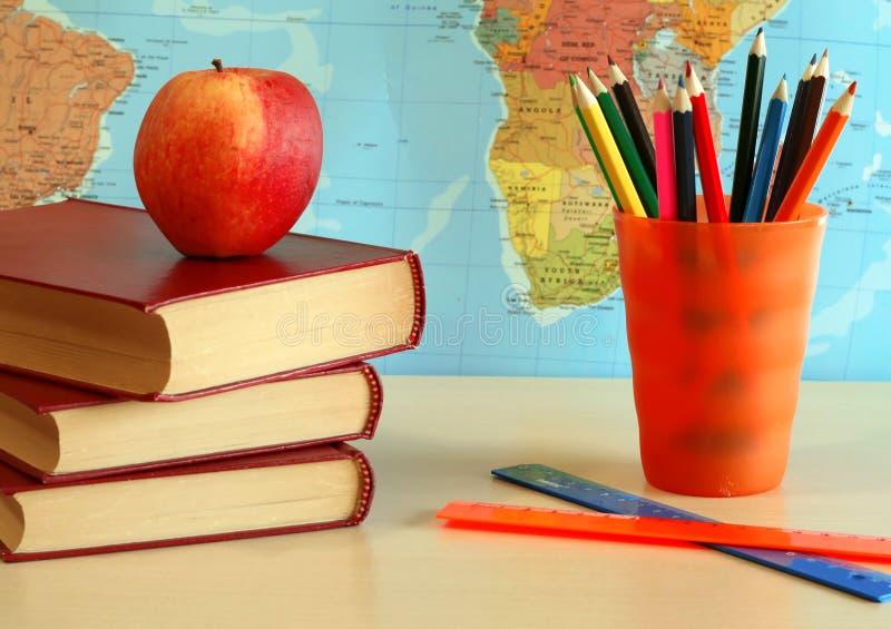 tarjeta de los libros, de los lápices, de la manzana y del mundo fotos de archivo