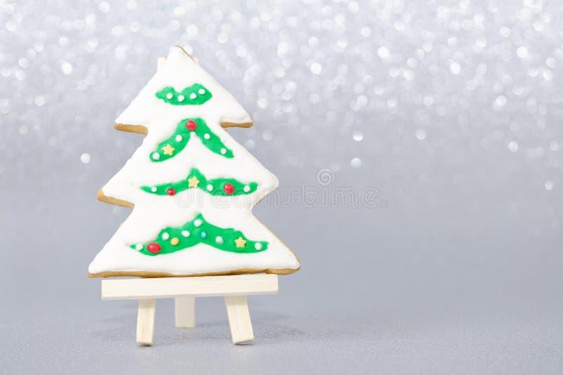 Tarjeta de Navidad con el árbol hecho a mano del pan de jengibre en fondo gris con el bokeh imagen de archivo