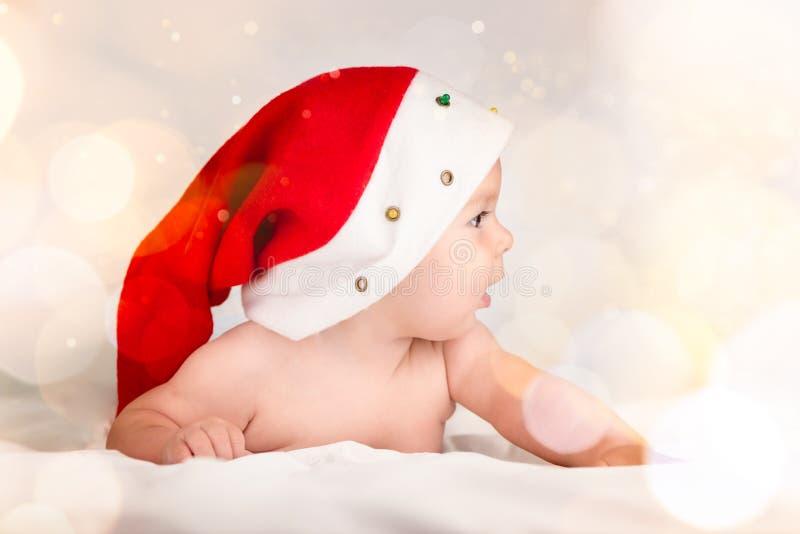 Tarjeta de Navidad con el bebé lindo con el sombrero de santa en fondo airoso beige del briht con el espacio de la copia imagen de archivo
