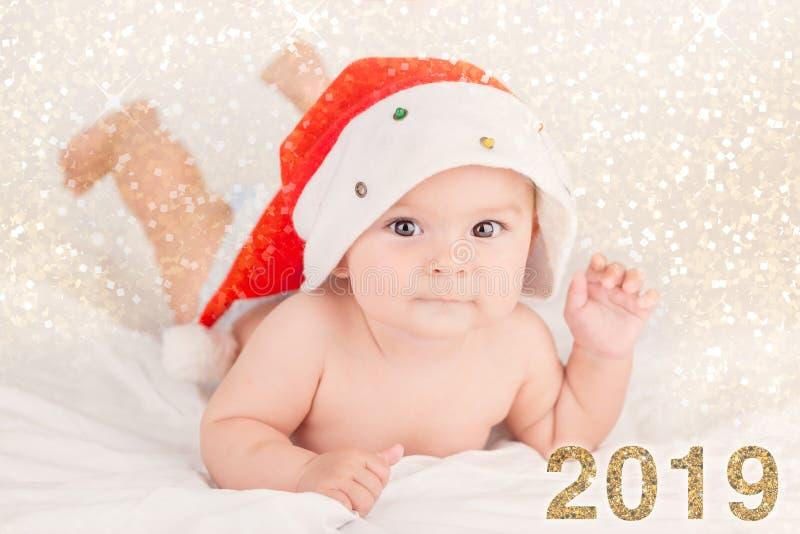 Tarjeta de Navidad con el bebé lindo con el sombrero de santa en fondo airoso beige del briht con el espacio de la copia imagen de archivo libre de regalías