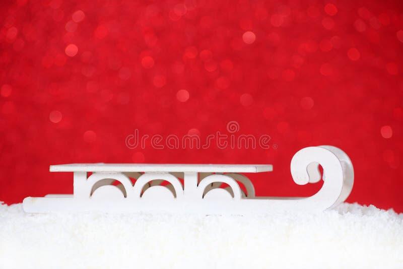 Tarjeta de Navidad con el trineo viejo en la nieve, fondo rojo, espacio de la copia fotografía de archivo libre de regalías
