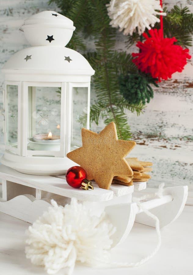 Tarjeta de Navidad con la linterna, las galletas y el trineo de la vela imágenes de archivo libres de regalías