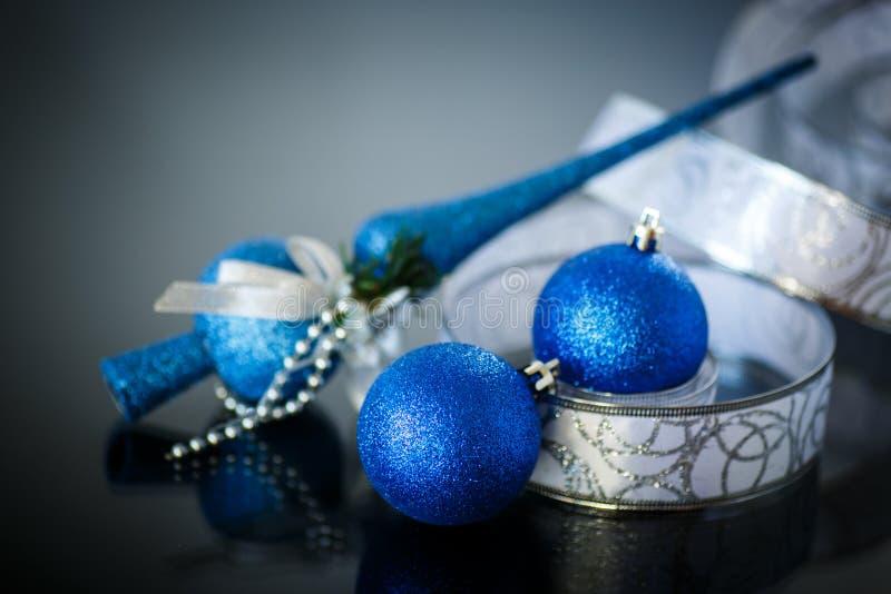 Tarjeta de Navidad con las bolas y la cinta azules imagenes de archivo