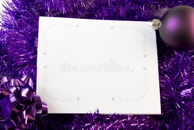 Tarjeta de Navidad con las decoraciones púrpuras foto de archivo