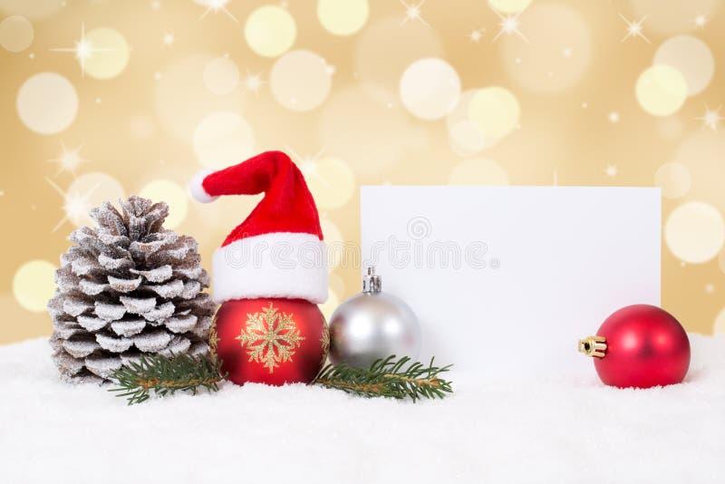 Tarjeta de Navidad con los ornamentos, fondo de oro, copyspace y fotografía de archivo