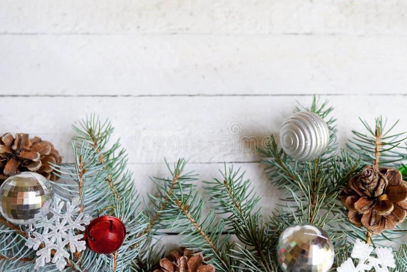 Tarjeta de Navidad, conos del pino y juguetes en fondo blanco de madera Endecha plana, espacio de la copia imagen de archivo libre de regalías