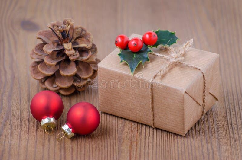 Tarjeta de Navidad del vintage con una caja de regalo y las bayas del acebo en fondo de madera imagen de archivo