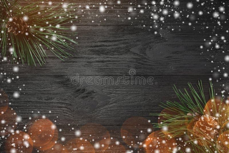 Tarjeta de Navidad El fondo de madera negro, con el pino ramifica, los conos del pino, visión superior Tarjeta de felicitación de fotografía de archivo