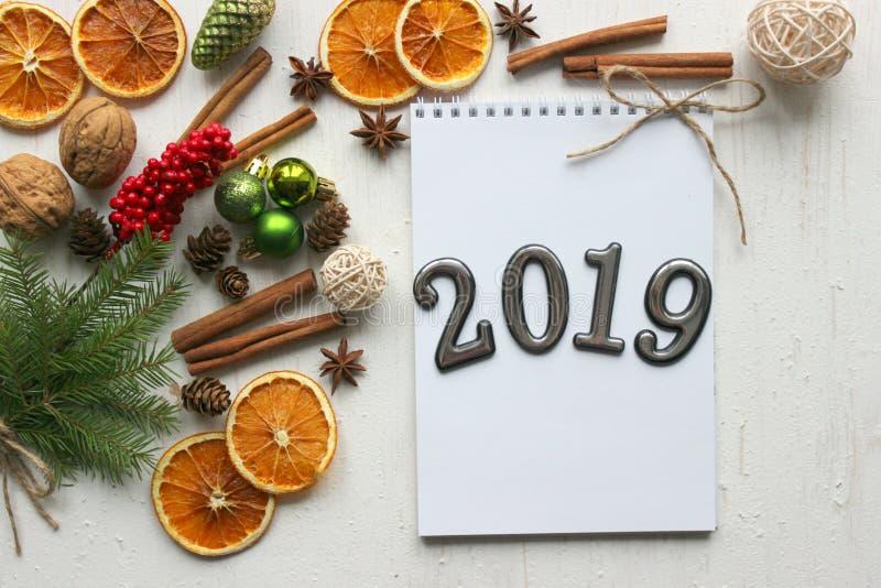 Tarjeta de Navidad, fecha 2019 del primer en un fondo del Libro Blanco rodeado por las decoraciones de la Navidad fotografía de archivo