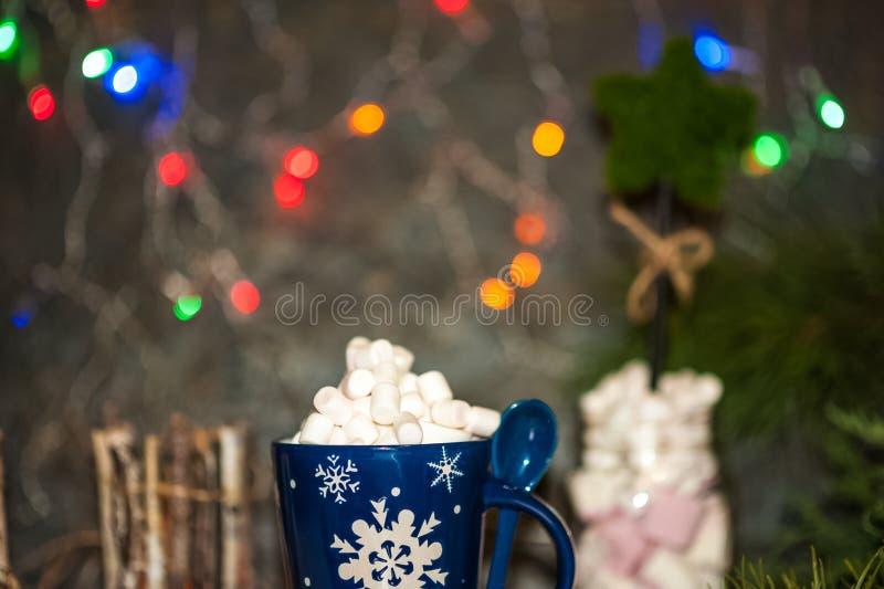 Tarjeta de Navidad, foto, fondo Taza azul con cacao y la melcocha en el fondo de las luces de la Navidad Soporte para una taza de imagenes de archivo