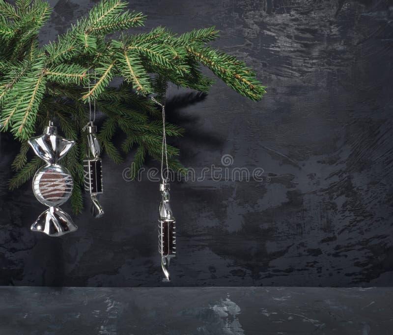 Tarjeta de Navidad Los juguetes de plata del abeto bajo la forma de caramelos cuelgan en una rama del abeto imagenes de archivo